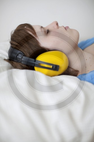 Junge Frau mit Gehoerschutz im Bett | Young woman with ear protection in bed