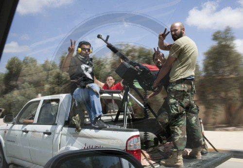 Rebels on a jeep with a mounted machine gun on a street in Benghazi. Benghazi / Libya. 13.06.2011